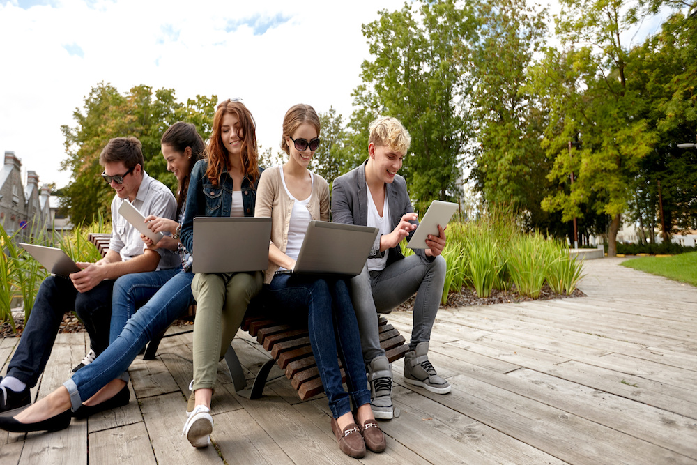 five people on labtops and tablets laughing in a park